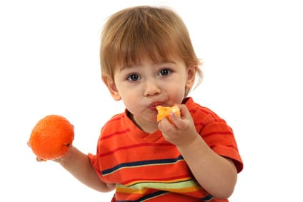 cute little boy eating tangerine